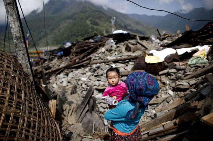 Bebé ao colo de uma mulher que contempla a devastação do terramoto do Nepal (EFE)