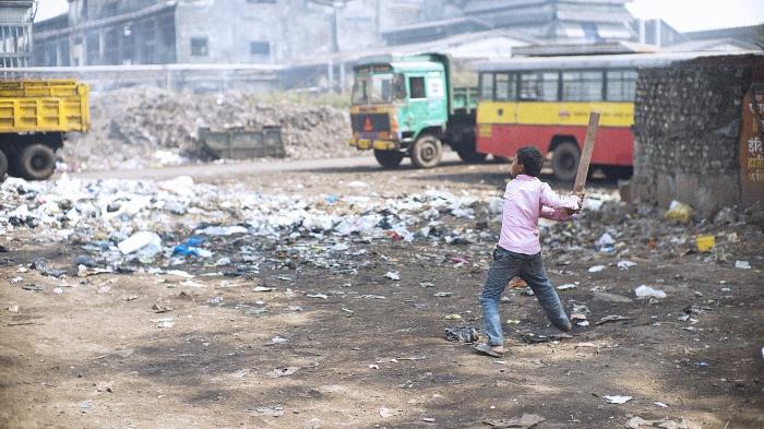 Menino em meio ao lixo. Foto de gary yim via Shutterstock.com